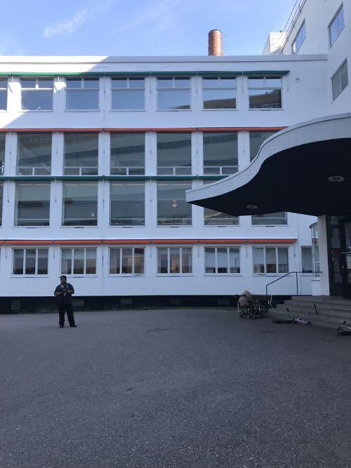 真白い外壁にオレンジとグリーンのワンポイントのラインの入った建物