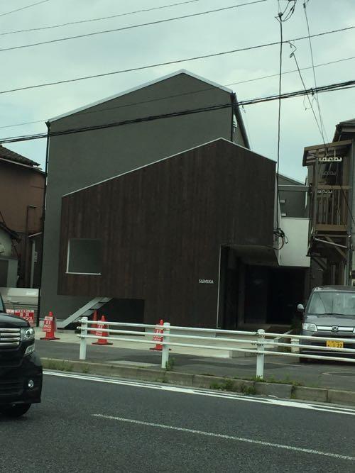 グレー色の塗り壁と木の外壁がおしゃれなお家の外観