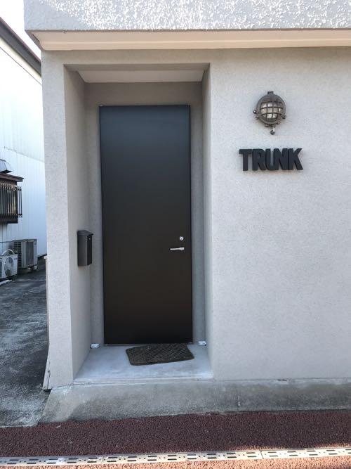 グレーの外壁にブラックのドア