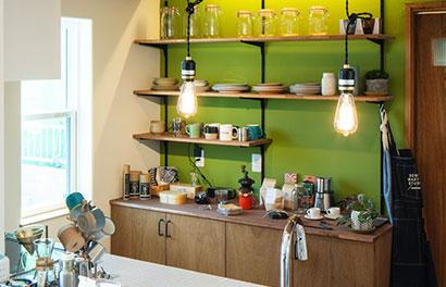 グリーンの壁がおしゃれな飾り棚のあるキッチン