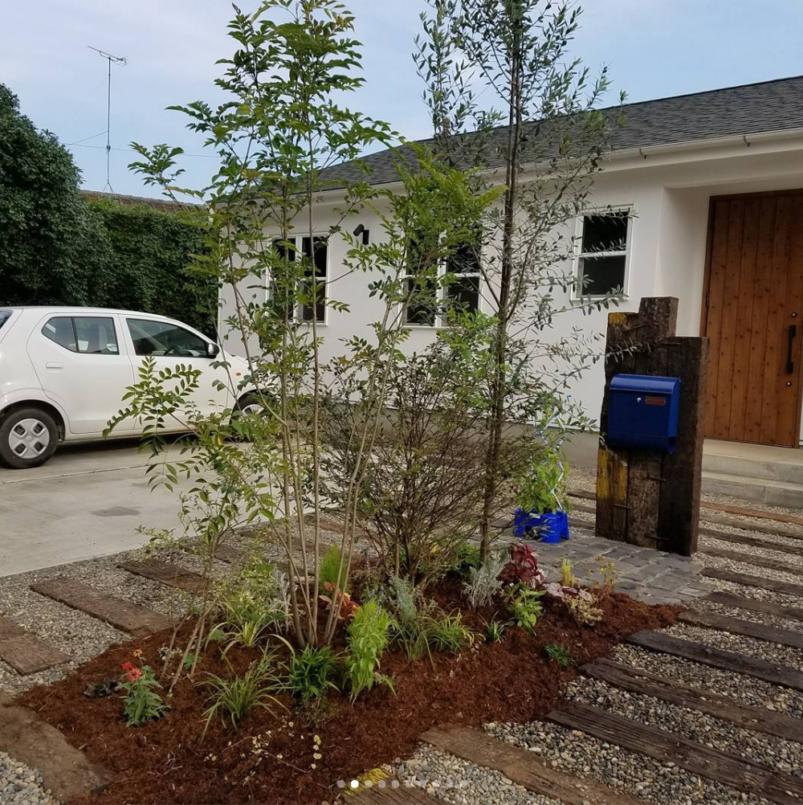 玄関先に植えられているグリーン達、砂利、枕木